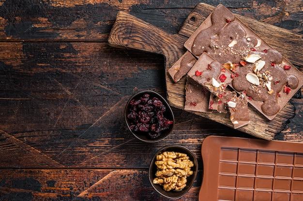 Czekolada mleczna homemade craft z orzechami laskowymi, orzeszkami ziemnymi, żurawiną i liofilizowanymi malinami. ciemne drewniane tło. widok z góry. skopiuj miejsce.