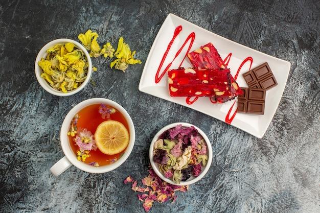 Czekolada na białym talerzu z herbatą ziołową w pobliżu miski suchych kwiatów na szarym podłożu