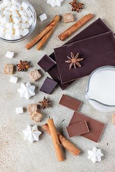 Czekolada, przyprawy, brązowy cukier, ptasie mleczko, beza i mleko. składniki na gorącą czekoladę.