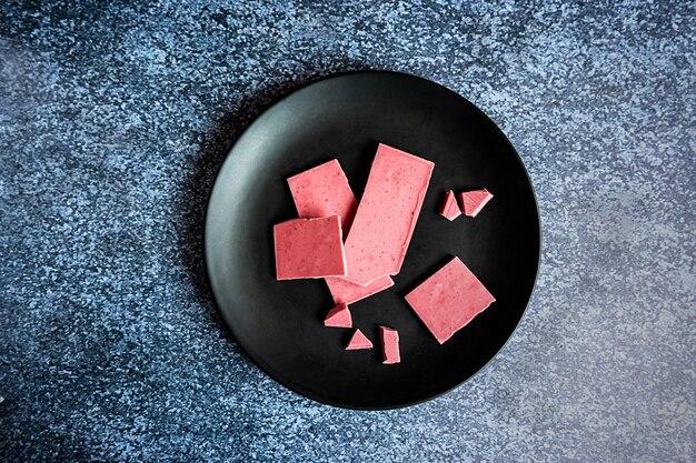 Czekolada różowa lub rubinowa, modny deser na czarnym talerzu