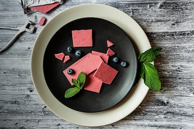Czekolada różowa lub rubinowa, modny nowoczesny deser podany na czarnym talerzu z listkami mięty, jagodami, szczypcami do cukru i tabliczką czekolady