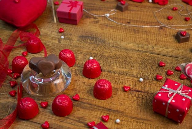 Czekolada serca w szklanej tablicy, cukierków i obecnych na drewnianym stole. dekoracje valentines