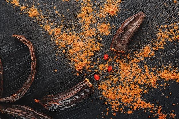 Czekolada świętojańska i proszek z owoców chleba świętojańskiego na ciemnej powierzchni