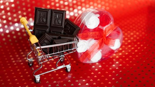 Czekolada w wózku na zakupy i prezent róże na czerwonym tle. wyprzedaż 14 lutego. kreatywna koncepcja minimalna