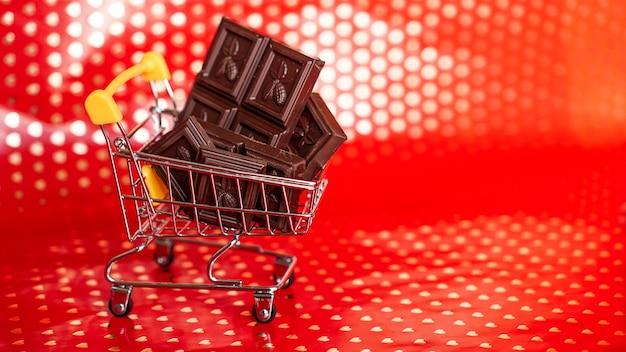 Czekolada w wózku na zakupy na czerwonym tle. wyprzedaż 14 lutego. kreatywna koncepcja minimalna