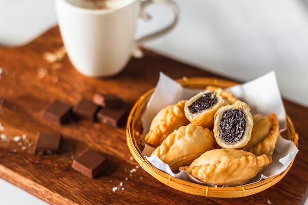 Czekolada wewnątrz puff pestry i filiżanka kawy na drewnianej desce do krojenia i składników