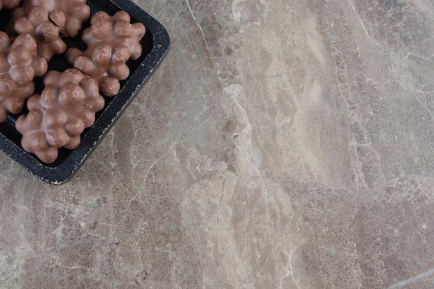 Czekolada z orzechami laskowymi na desce na marmurze.
