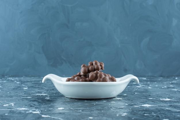 Czekolada z orzechami laskowymi w misce, na niebieskim stole.