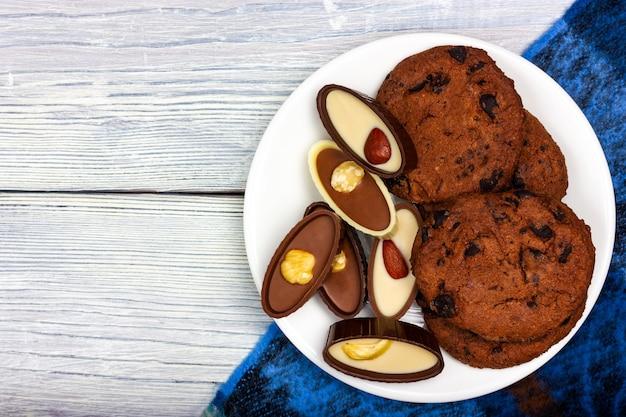 Czekoladki i chrupiące ciasteczka z kawałkami czekolady leżą na białym talerzu w stylu prowansalskim