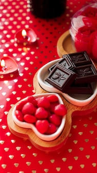 Czekoladki i słodycze na talerzach w kształcie serca. świąteczne nakrycie stołu na randkę zakochanych. czerwone tło. zdjęcie pionowe