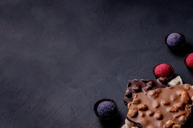 Czekoladki tło. czekolada. asortyment wykwintnych czekoladek w białej, gorzkiej i mlecznej czekoladzie. słodycze czekoladowe praline.