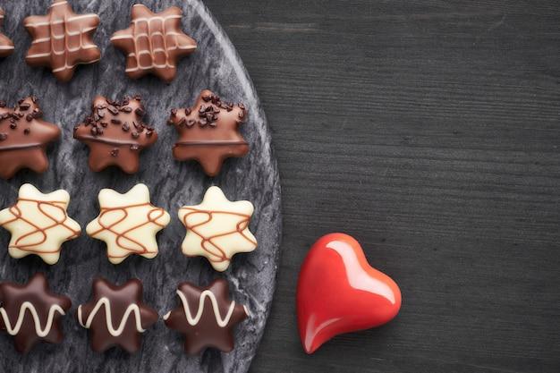 Czekoladki w kształcie gwiazdy na ciemnym stole i czerwonym ceramicznym sercu