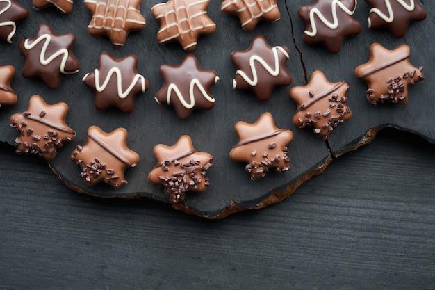 Czekoladki w kształcie gwiazdy na ciemnym tle z teksturą