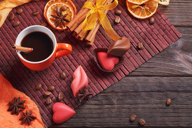 Czekoladki w kształcie serca i ust, pomarańczowy kubek czarnej kawy, czarne palone ziarna kawy, suszone plasterki cytryny z przyprawami cynamonem i anyżem na ciemnym tle. koncepcja deseru czekoladowego