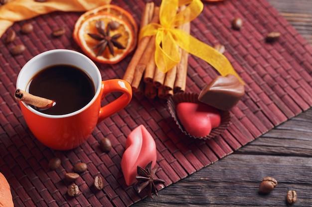 Czekoladki w kształcie serca i ust, pomarańczowy kubek czarnej kawy, prażone ziarna kawy, suszone plasterki cytryny z przyprawami cynamonem i anyżem na ciemnym tle. koncepcja deseru czekoladowego
