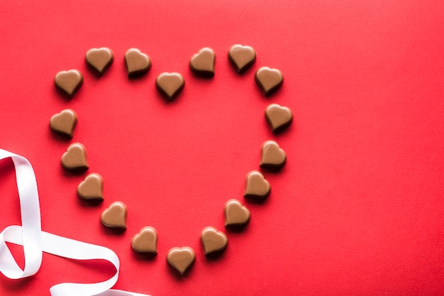 Czekoladki w kształcie serca na czerwonym tle na walentynki