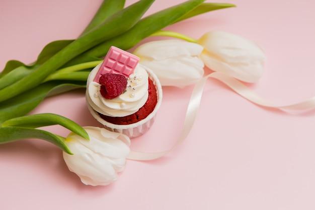 Czekoladowa babeczka i białe tulipany na różowej przestrzeni
