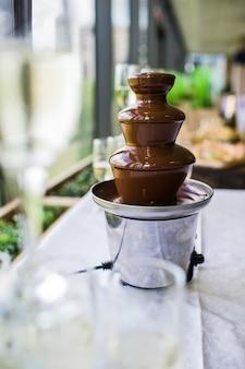 Czekoladowa fontanna na stole w formie bufetu w restauracji