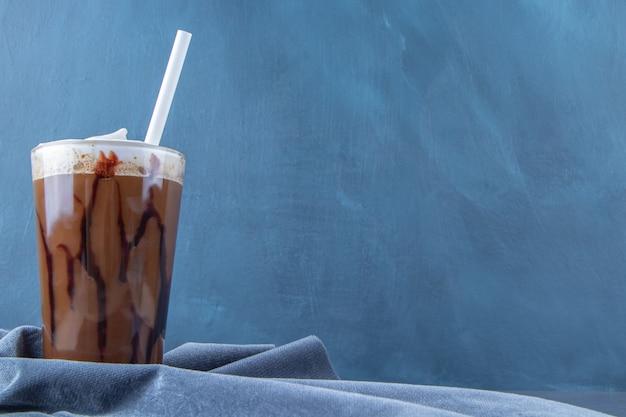 Czekoladowa mokka w szklance na kawałku tkaniny, na niebieskim stole.