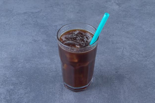 Czekoladowa mokka w szklance ze słomką, na niebieskim stole.