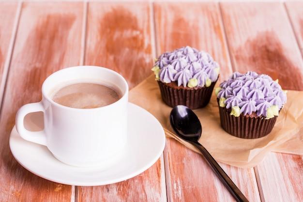 Czekoladowa pyszna babeczka z kremową i aromatyczną kawą z mlekiem na białym drewnianym stole.