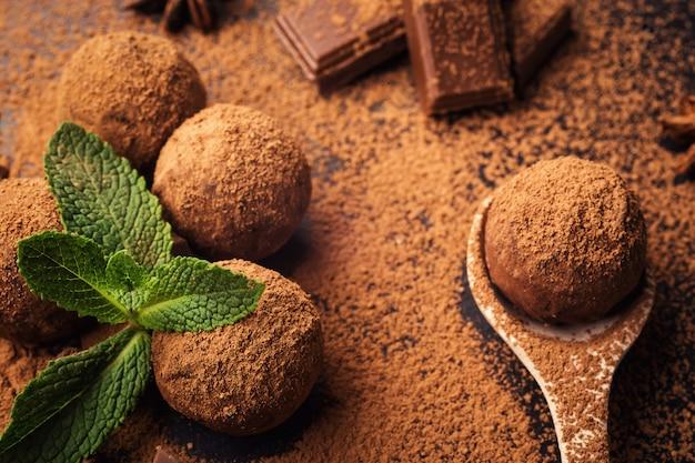 Czekoladowa trufla, truflowe cukierki czekoladowe z proszkiem kakaowym. domowe kulki świeżej energii z czekoladą. gourmet różne trufle wykonane przez chocolatiera. kawałki czekolady i ziaren kawy