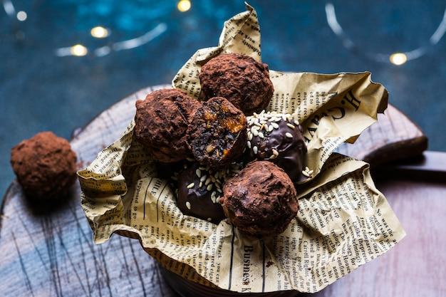 Czekoladowa trufla z kawałkami czekolady i latającym kakao w proszku na ciemnym tle. zdrowe cukierki. wegańskie cukierki. deser noworoczny. świąteczny deser. walentynki