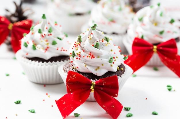 Czekoladowe babeczki dekorowali białą śmietankę i jedlinowych drzew na białym talerzu. świąteczne słodycze. deser noworoczny