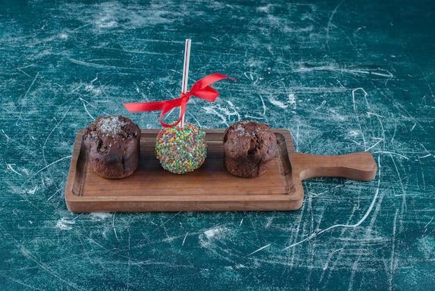 Czekoladowe babeczki i lizak powlekany cukierki na pokładzie na niebieskim tle. wysokiej jakości zdjęcie