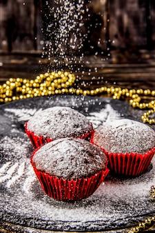 Czekoladowe babeczki na ciemnym tle z cukrem pudrem