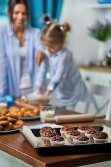Czekoladowe babeczki na tacy w kuchni, w ścianie mama i córka pieką ciasteczka