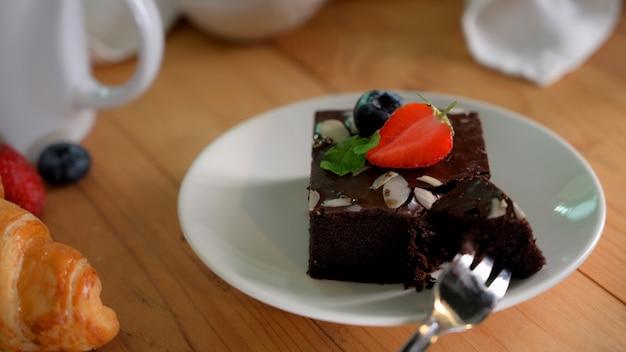 Czekoladowe brownie na białym talerzu z liściem mięty na wierzchu