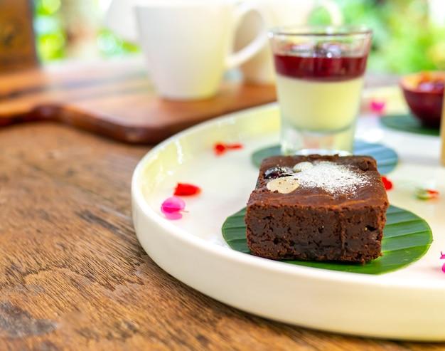 Czekoladowe brownie posypane migdałami umieszczone na białym talerzu na drewnianym stole.