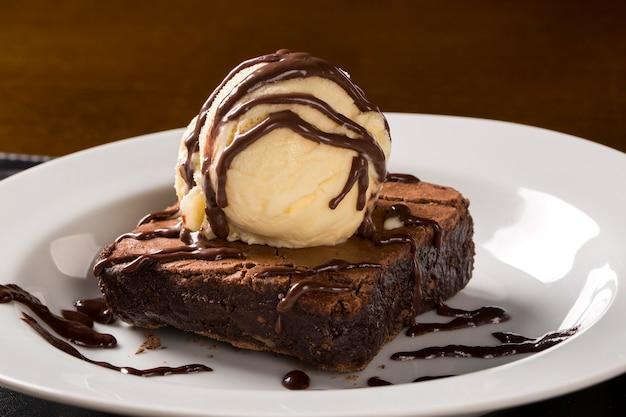 Czekoladowe brownie z lodami waniliowymi na talerzu.