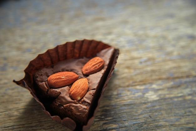 Czekoladowe brownie z migdałową polewą na zardzewiałym drewnianym stole