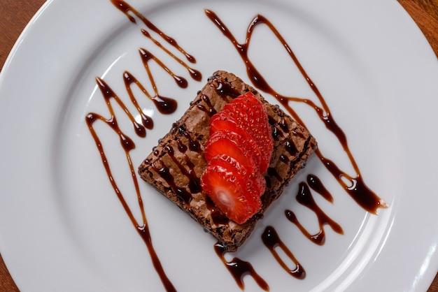 Czekoladowe brownie z pokrojonymi truskawkami na białym talerzu widok z góry z bliska