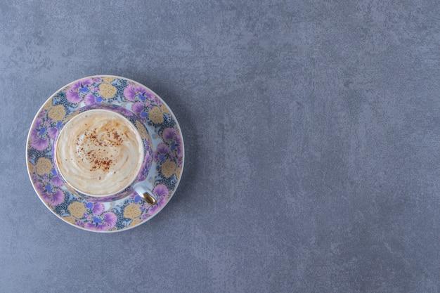 Czekoladowe cappuccino w filiżance na spodku, na niebieskim stole.