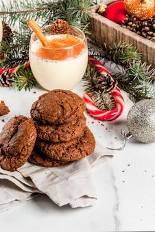 Czekoladowe ciasteczka crinkle na boże narodzenie, z ajerkoniakiem, trzciną cukrową, choinką i dekoracją świąteczną, na białym marmurowym stole,