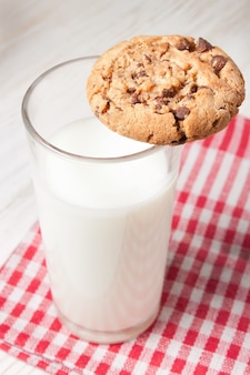 Czekoladowe ciasteczka i szklankę mleka na serwetce na białym drewnianym stole