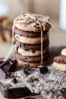 Czekoladowe ciasteczka na drewnianym stole rustykalne. domowe ciasteczka. stos smaczne ciasteczka czekoladowe