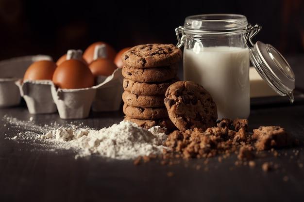 Czekoladowe ciasteczka na rustykalnym drewnianym stole z butelką mleka, białej mąki, świeżych jajek, masła i okruchów. zdrowy deser.