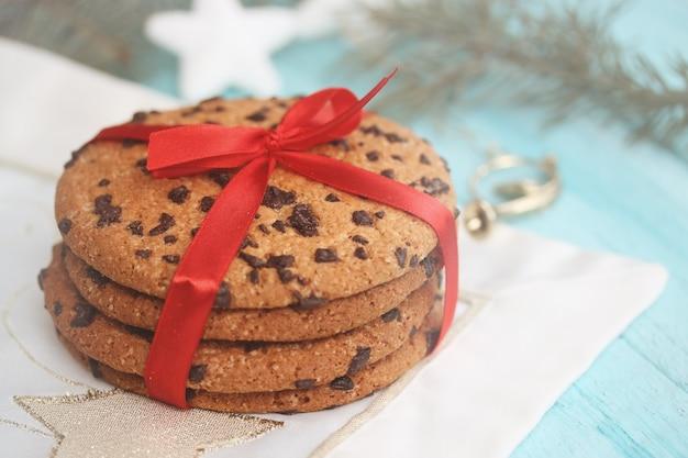 Czekoladowe ciasteczka przewiązane czerwoną wstążką. prezent na drewnianym tle. boże narodzenie tło z miejsca na kopię.