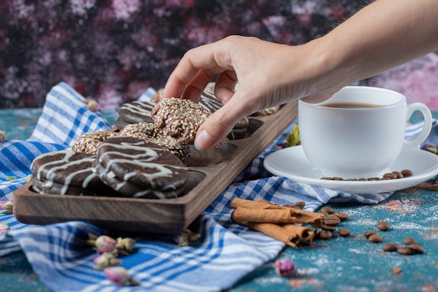 Czekoladowe ciasteczka sezamowe podawane z kubkiem napoju.