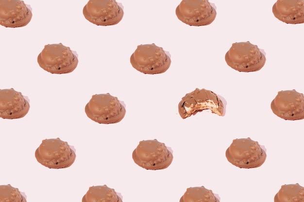 Czekoladowe ciasteczka ułożone we wzór, w którym jedno ciasteczko jest odgryzane na różowym tle. koncepcja party słodkie jedzenie.