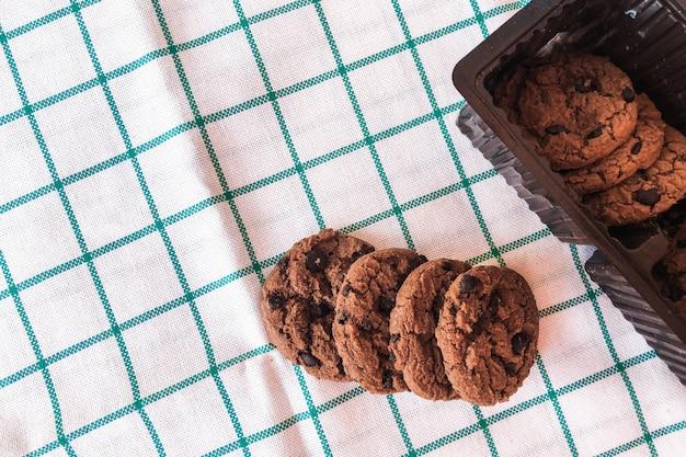 Czekoladowe ciasteczka w opakowaniach na tle tkaniny.