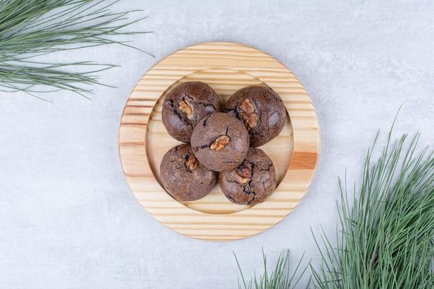 Czekoladowe ciasteczka z jądrami orzecha włoskiego na drewnianym talerzu. zdjęcie wysokiej jakości