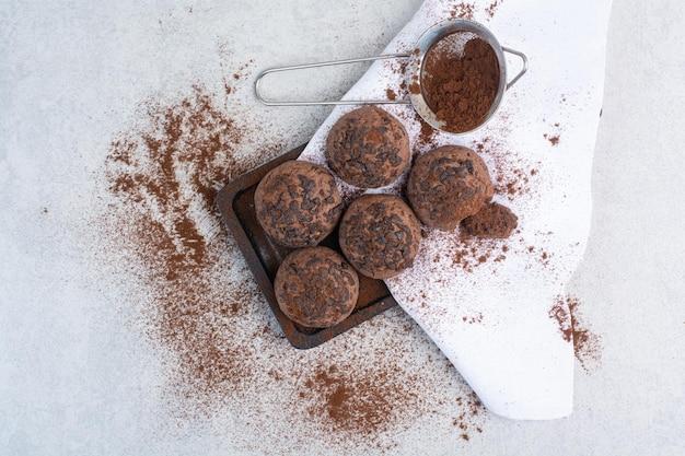 Czekoladowe ciasteczka z proszkiem kakaowym na drewnianym talerzu. zdjęcie wysokiej jakości