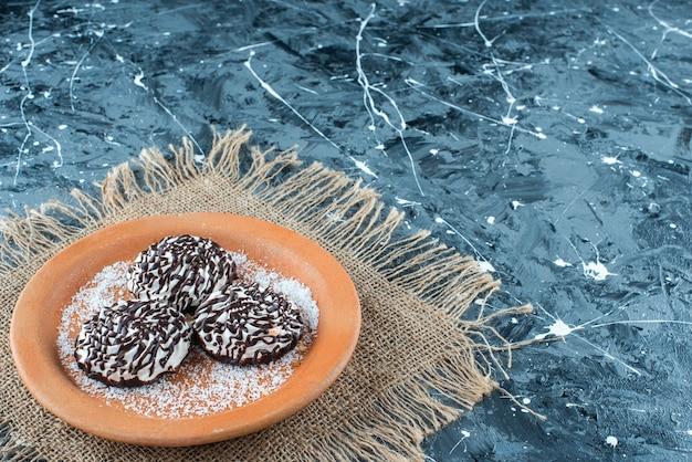 Czekoladowe ciasteczko na glinianym talerzu na fakturze, na niebieskim stole.