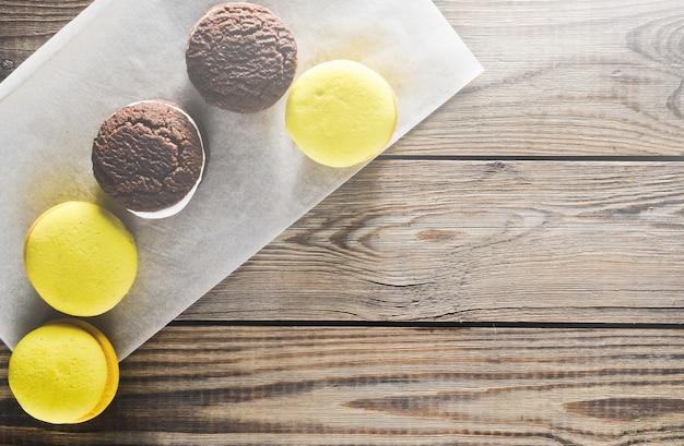 Czekoladowe ciastka i makaroniki na rustykalnym drewnianym stole.