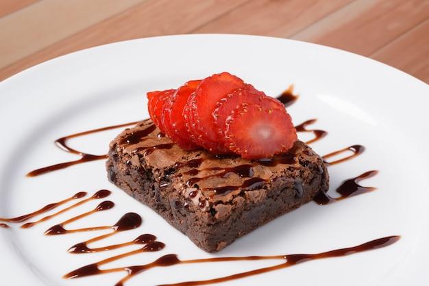 Czekoladowe ciastko z pokrojonymi truskawkami na białym talerzu nad drewnianym stołem.